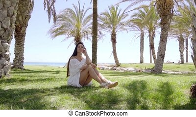 Single woman sitting among palm trees - Smiling cute woman...