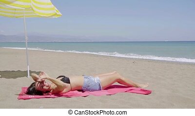 Trendy young woman sunbathing on the beach in a skimpy pair...