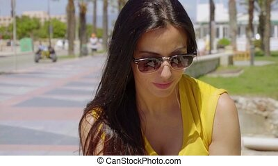 Thoughtful young woman wearing sunglasses