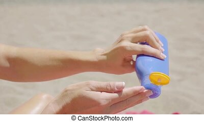Young woman applying suntan lotion emptying it from the...