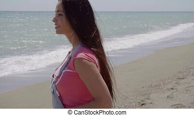 Relaxing beautiful woman walking along beach - Single...