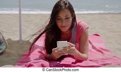 Woman laying on beach using cell phone - Cute grinning woman...