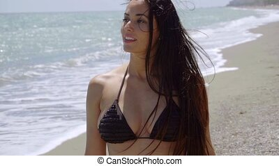 Attractive woman walking on the beach in a black bikini...