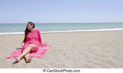Graceful young woman sunbathing on the beach sitting on a...