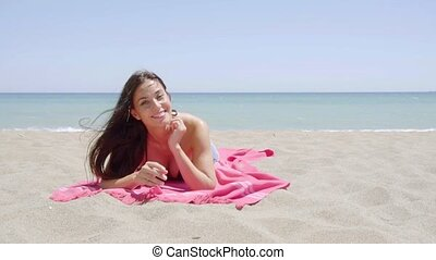 Happy young woman relaxing at the seaside lying on a pink...
