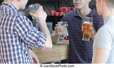 Close up of three friends drinking beverages at the bar -...