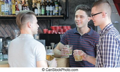 Men drink beverages at the bar counter - Three young men...