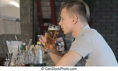 Man smiles after sip of beer - Blond man smiling after sip...
