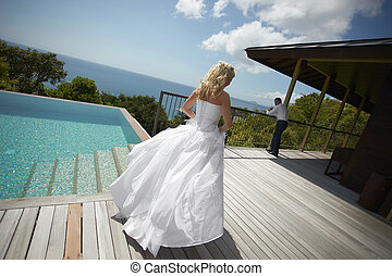 Lovely bride coming across pool area before wedding Warm...