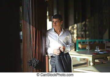 Handsome young man standing outside restaurant on terrace.
