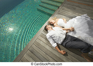 Beautiful young couple lying near pool with mind waves -...