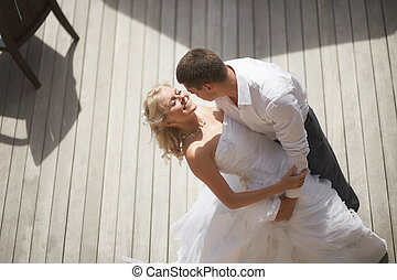 Lovely, gorgeous couple kissing close to pool area after...