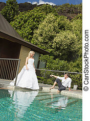 Beautiful young couple lying close to pool before wedding...