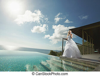 Beautiful young couple standing close to pool before wedding...