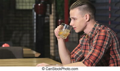 Blonde man drinks alcohol at the bar - Blond man drinking...