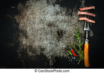 Slices of beef steak on meat fork on dark background