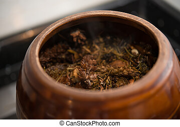 medicinal herbs in enamel pot close up