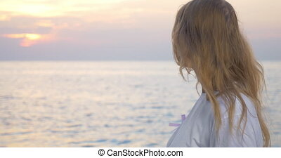 Woman with pink awareness ribbon by the sea - Young blond...