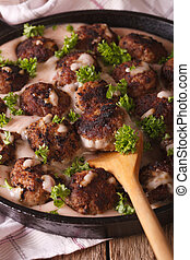 Swedish meatballs in a creamy cowberry sauce closeup on a...