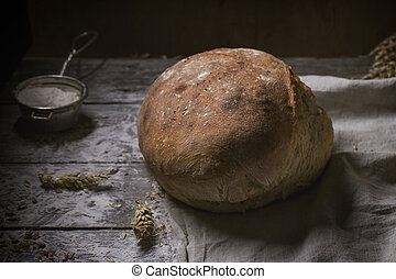 Artisan bread over wooden table with flour and ears of wheat