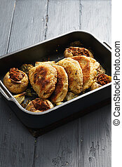 Oven tray with cordon bleu cutlets and stuffed vegetables on...