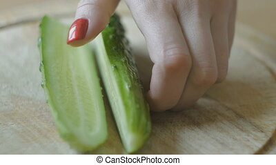 Girl's hands with red nails cut cucumber into slices