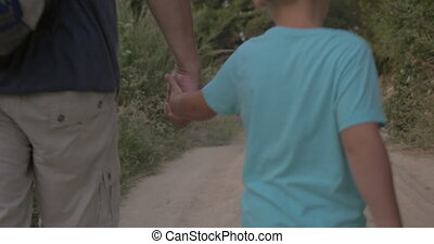Child and grandpa hiking in the woods - Steadicam back shot...