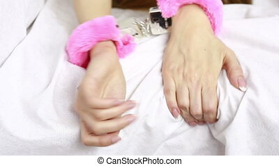 female hands in leather handcuffs sex toys grabs the white...
