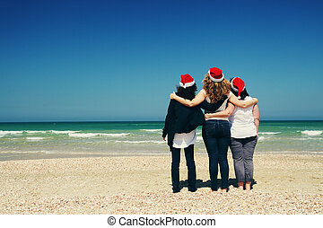 Three beautiful women wearing christmas hat walking on the...