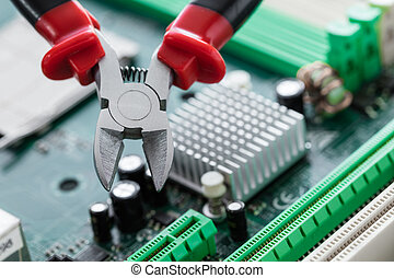 nippers close-up on computer circuit board background