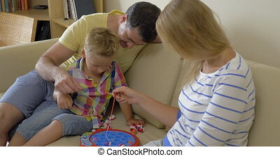 Parents and child playing fishing game at home