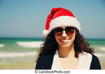 beautiful woman wearing christmas hat walking on the seaside