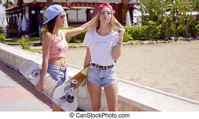 Carefree friends near beach with wind blown hair holding a...