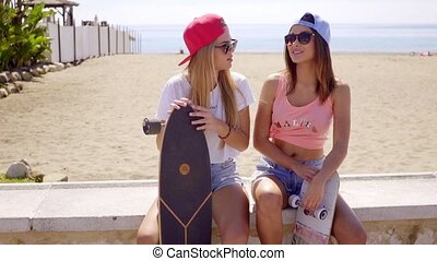 Two good looking female skating friends with caps - Two good...