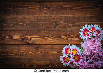 Flowers on brown wooden table, top view