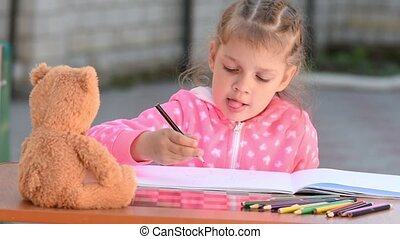 Five-year girl with enthusiasm draws a teddy bear sitting in...