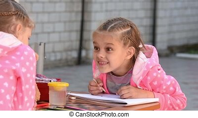 Seven-year girl drawing in an album emotionally speaks with...