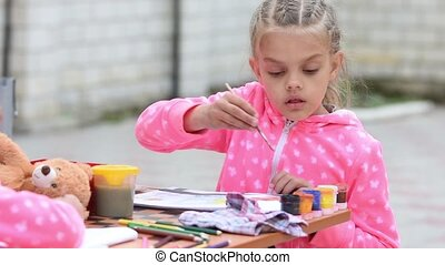 Seven-year girl hard dunks brush in a jar with watercolor...