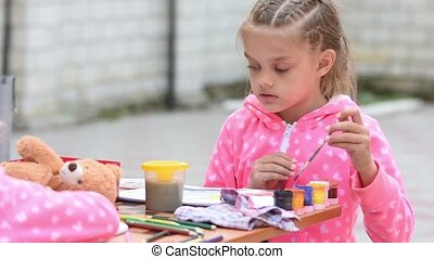 Seven-year girl choose the right color ink drawing in an...