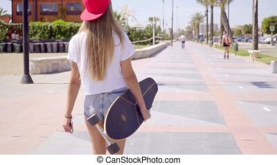 Rear view of skateboarder walking on sidewalk - Rear view on...