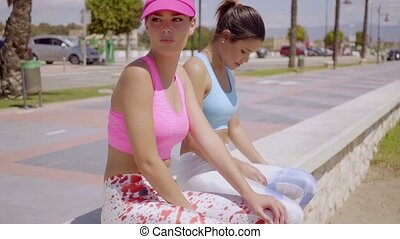 Two young women taking a rest from a workout - Two...