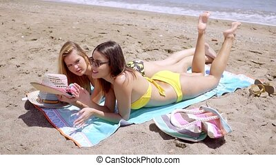 Pretty young female students enjoying the beach - Two pretty...