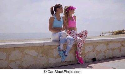 Two sexy trendy young women sitting on a low wall...