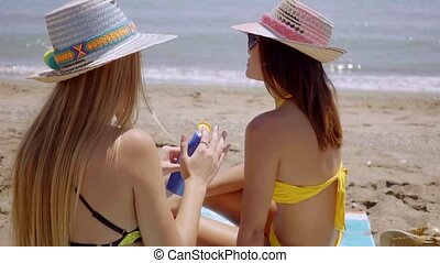 Young woman applying sunscreen on a friend - Young woman...