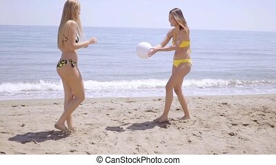 Two young female friends playing beach ball - Two young...