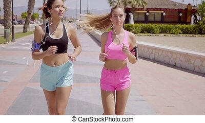 Two sporty young women out jogging together along a...