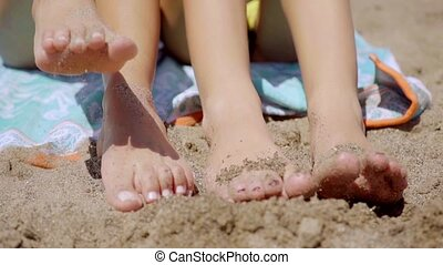 Bare feet of two young women in beach sand as they sit on...