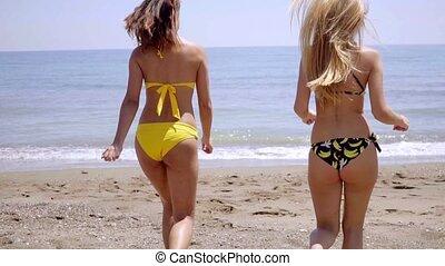 Young women in bikinis approaching the sea
