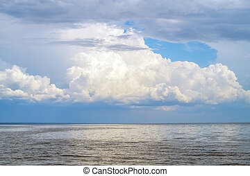 Big lake with big fluffy cloud above nature background.