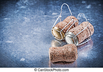 Alcohol cork taps with twisted wires on metallic background